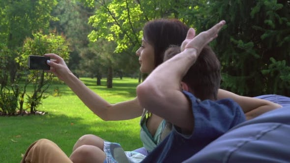 Thumbnail for Young Couple Sitting On The Ottoman In The Park And Makes Selfie.