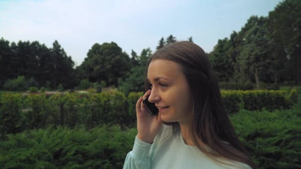 Thumbnail for Young Brunette Girl Slowly Passes Through The Park And Talking On The Phone.