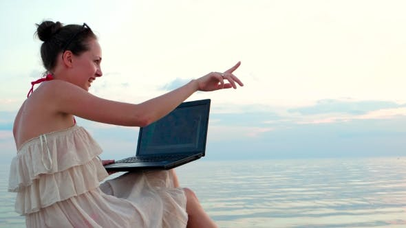 Thumbnail for Girl With a Laptop Talking On Skype With a Loved Boyfriend Showing Coastline.