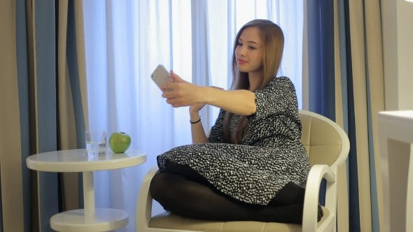 Thumbnail for Pretty Girl Make Selfy Using Smartphone Seating In Luxury Hotel Room