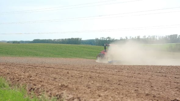 Thumbnail for An Agricultural Tractor Plowing a Field. Hills And a Forest At The Background. Soil Dust All Over