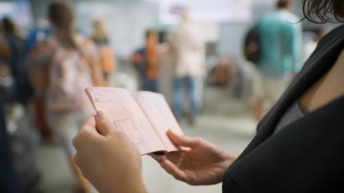 A Young Woman Is Looking At Her Visa In The Passport