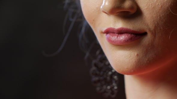 Thumbnail for Rosa lächelnde Lippen und Kinn der jungen schlanken Frau, Studio Shot auf schwarzem Hintergrund