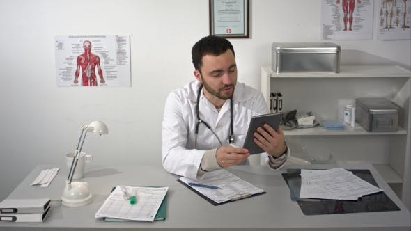 Thumbnail for Male Doctor Having Video Conference Useing Tablet Gadget
