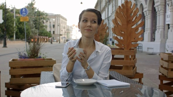 Thumbnail for Happy Pensive Woman Drinking In a Coffee Shop Terrace In The Street