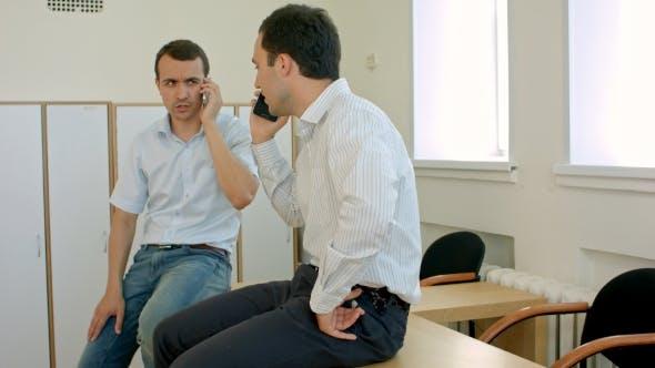 Thumbnail for Zwei lächelnde Studenten mit Handy in Händen Haben Angenehme Unterhaltung im Zimmer