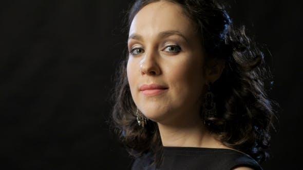 Thumbnail for Glamouröse junge Frau mit welliges dunkles Haar Blick auf Kamera und Lächeln,