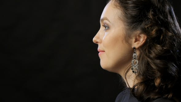 Thumbnail for Profile Of Brunette With Wavy Hair And Large Silver Earring, Turning Head, Looking At Camera