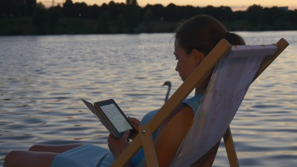 Thumbnail for Girl Reads E-book At Sunset On The Sunbed Near Water