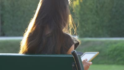 Female With Sunlight On Her Hair Reads E-book In The Park