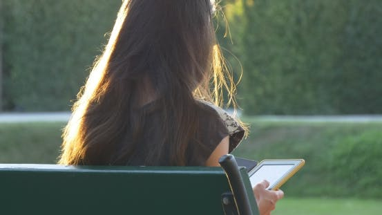 Thumbnail for Female With Sunlight On Her Hair Reads E-book In The Park