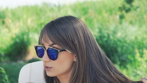 The Girl Undressing Sunglasses And Smiling To The Camera