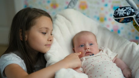 Thumbnail for The Little Girl Looks At Her Baby Sister