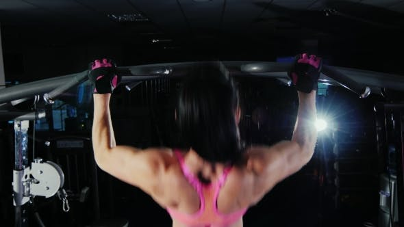 Thumbnail for Attractive Fitness Woman Pulls On The Bar In The Gym. Female Bodybuilding. Bacl View