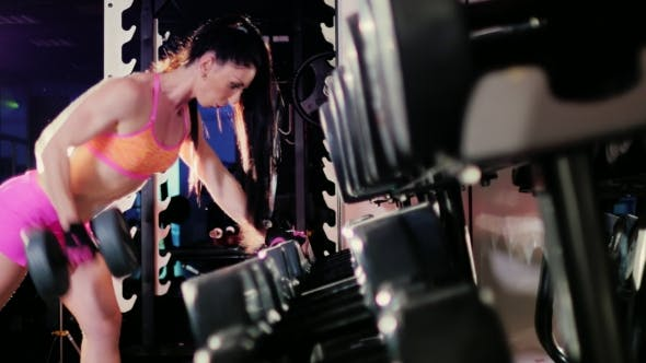 Thumbnail for Female Athlete Doing Exercise With a Dumbbell In The Gym.