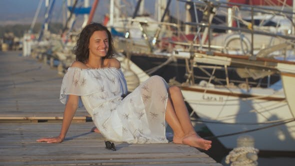 Thumbnail for Beautiful Happy Woman Sitting On a Pier On a Summer Day