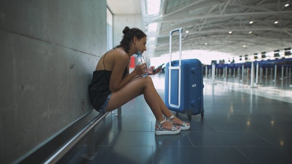 Thumbnail for Passenger, Woman Siting In The Airport, Waiting For Her Flight Using Her Phone
