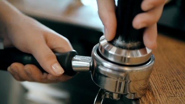 Thumbnail for Barista Hands Using a Tamper To Press Freshly Ground Coffee Into a Coffee Tablet