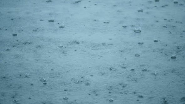 Thumbnail for Rain Drops Rippling In a Puddle With Blue Sky Reflection
