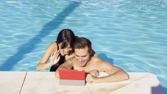 Thumbnail for Smiling Couple In Swimming Pool Use Digital Device