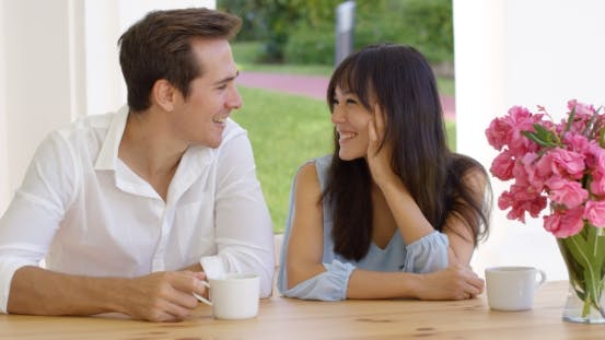 Thumbnail for Laughing Young Adult Couple Sitting At Table