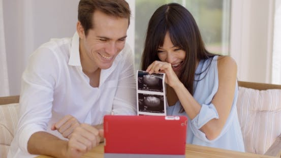 Thumbnail for Blushing Couple Showing Off Ultrasound Pictures