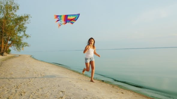 Thumbnail for Carefree Girl Runs Along The Beach, Playing With a Kite
