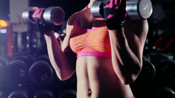 Thumbnail for Female Athlete Doing Exercise With a Dumbbell In The Gym. In The Spotlight