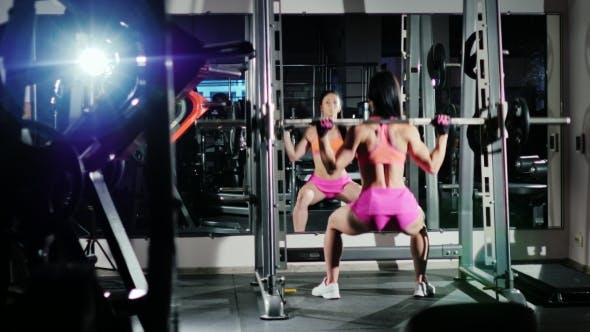 Cover Image for Athletic Woman Squats With a Barbell. Motivation In Sport. Back View