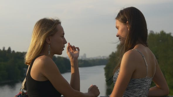 Thumbnail for Young Women Chatting Standing On a Bridge Across The River