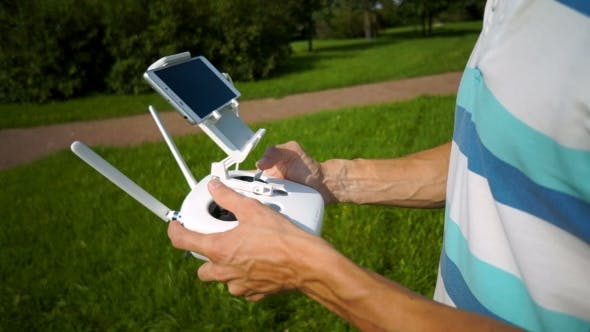 a young man in a t-shirt uses a remote controller to control the quadcopter
