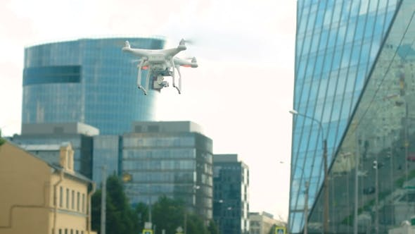 Thumbnail for A Radio-controlled Quadcopter Hovers Over a Street In The City