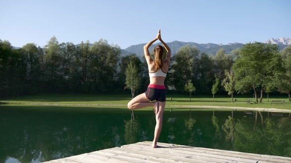 Fit Young Woman In Yoga Tree Pose