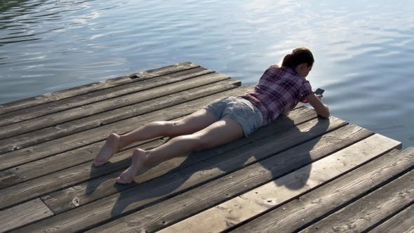 Thumbnail for Woman Browses Mobile Phone Lying on a Wooden Pier