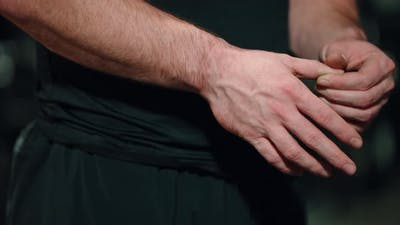 Hands of Strong Man Checking Fingers After Workout