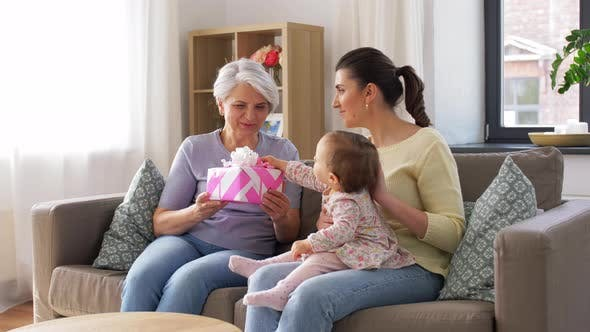 Mother and Daughter Giving Grandmother Present