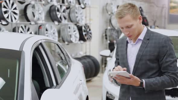 Thumbnail for Man Seller with Tablet Shows the Car in the Showroom