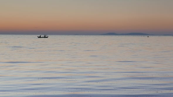 Thumbnail for Calm Sea With a Silhouetted Rowing Boat at Sunset.
