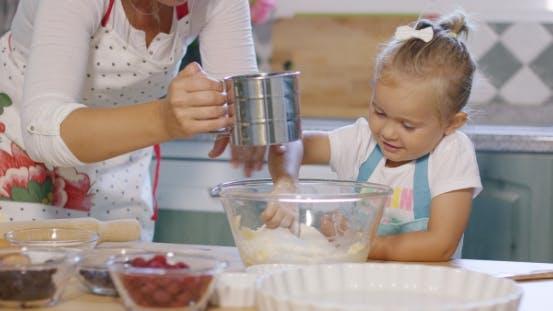 Thumbnail for Cute Little Girl Helping Her Mother Bake a Tart