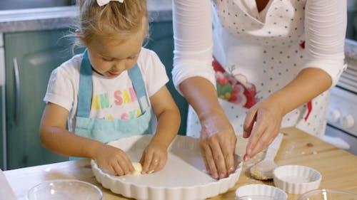 Cute Little Girl Greasing a Baking Dish