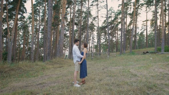 Thumbnail for Beautiful Man And Woman Embracing Standing In a Clearing In The Middle Of a Pine Forest.