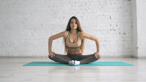 Thumbnail for Beautiful Young Woman Doing the Butterfly Stretch at Fitness Studio