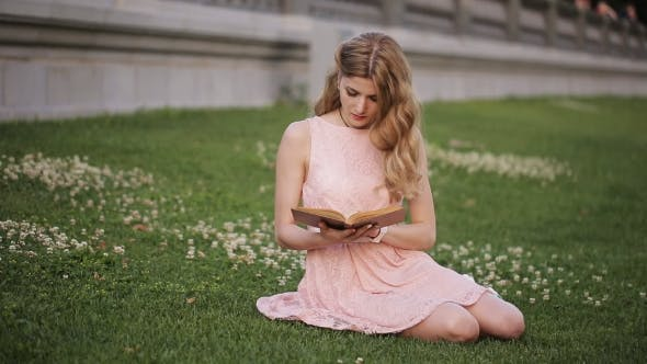 Thumbnail for The Girl on the Lawn in the Park Reading a Fascinating Book and Laughs