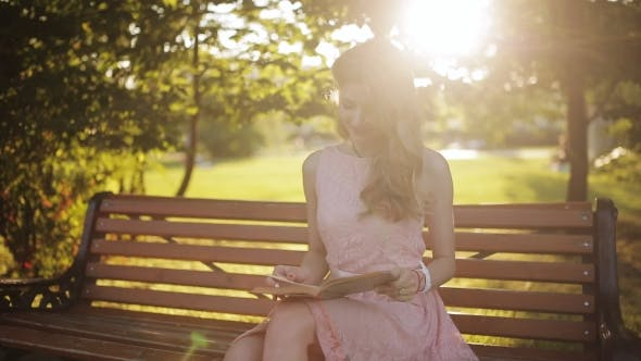 Thumbnail for Young Woman Sitting On The Bench In a Park And Reading a Book. Beautiful European Girl Studying