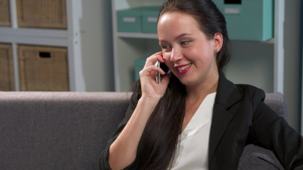 Cover Image for Cheerful Woman Talking By Phone In Office