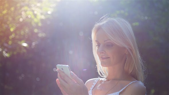 Thumbnail for Beautiful Girl Using SmartPhone Enjoying the Sun in City Park 2