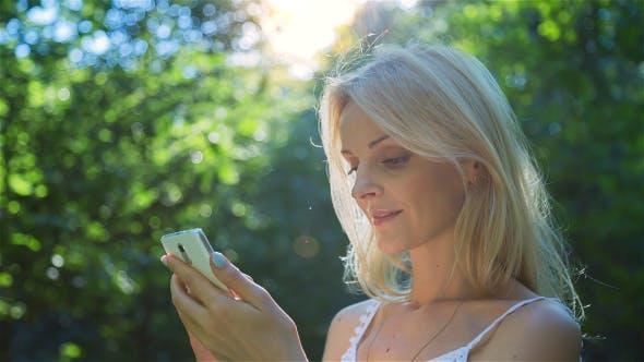 Thumbnail for Beautiful Girl Using SmartPhone Enjoying the Sun in City Park 3