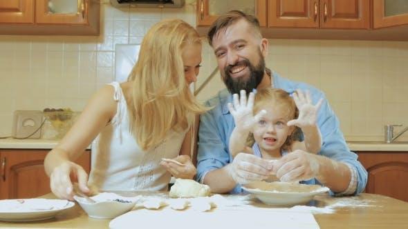 Thumbnail for Glückliche Familie Mutter, Vater und Kleine Tochter In der Küche Vorbereitung Kuchen aus dem Test.