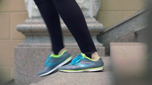 Woman Legs In Sport Shoes Walking Down Stairs. Legs In Running Shoes