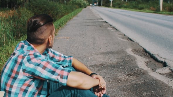 Thumbnail for Young Boy Sitting At Road Hold Ear Of Grass In Mouth. Wait. Travel. Hitchhiking